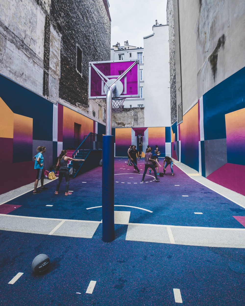 group of men playing basketball on alleyway