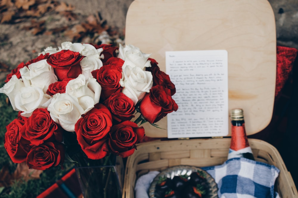 red and white roses beside beige wicker basket