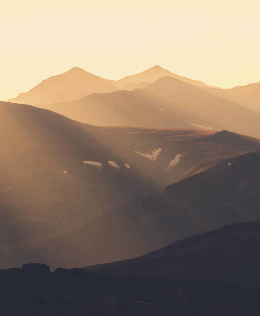 sun shining over mountain ranges