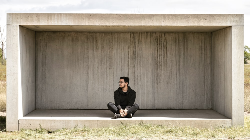 man sitting on gray concrete shed during daytime