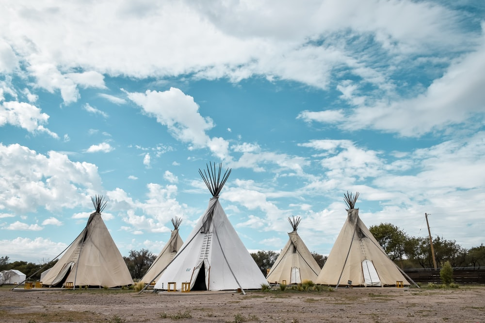 five tippi tents during day time