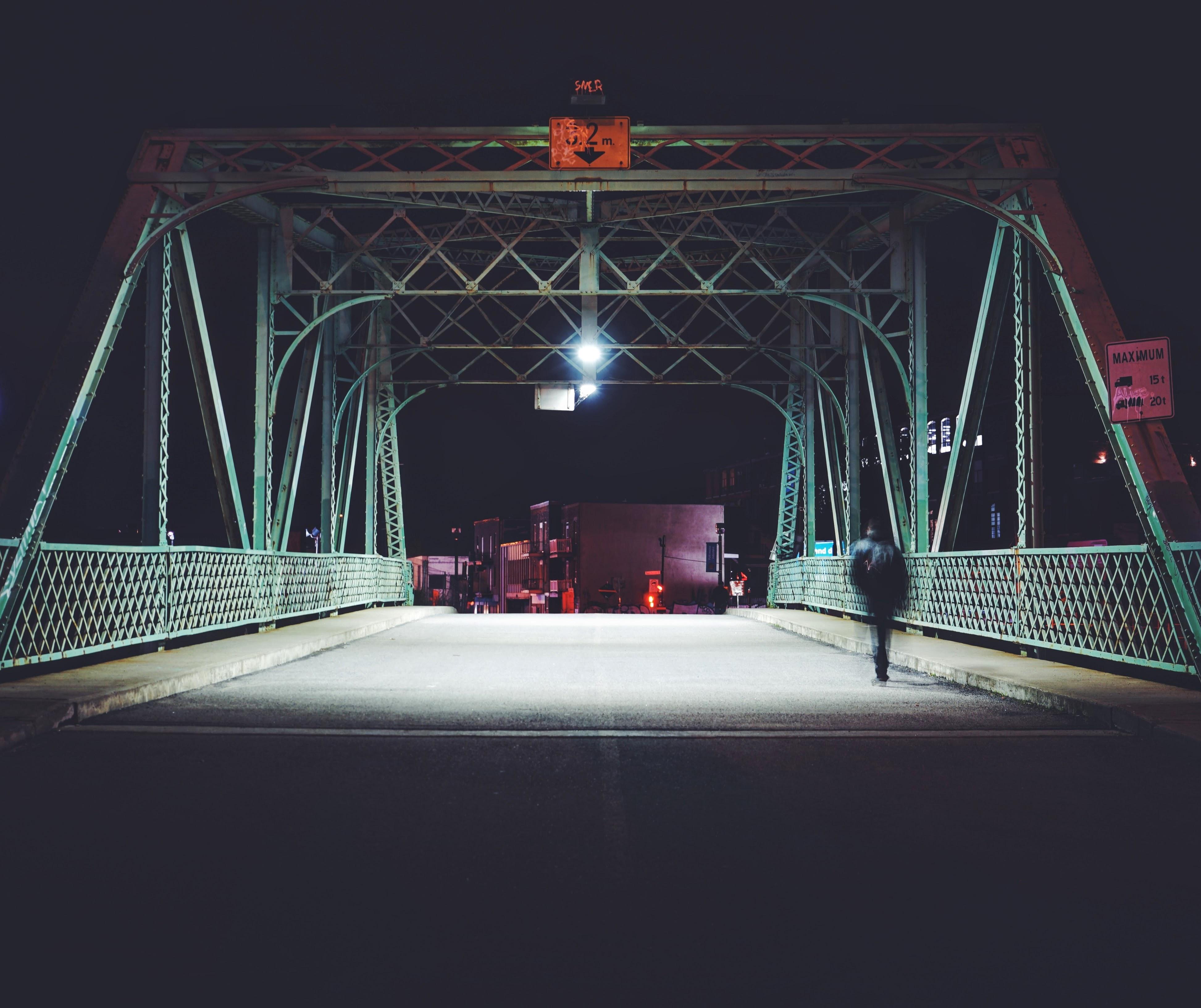 man walking on steel bridge