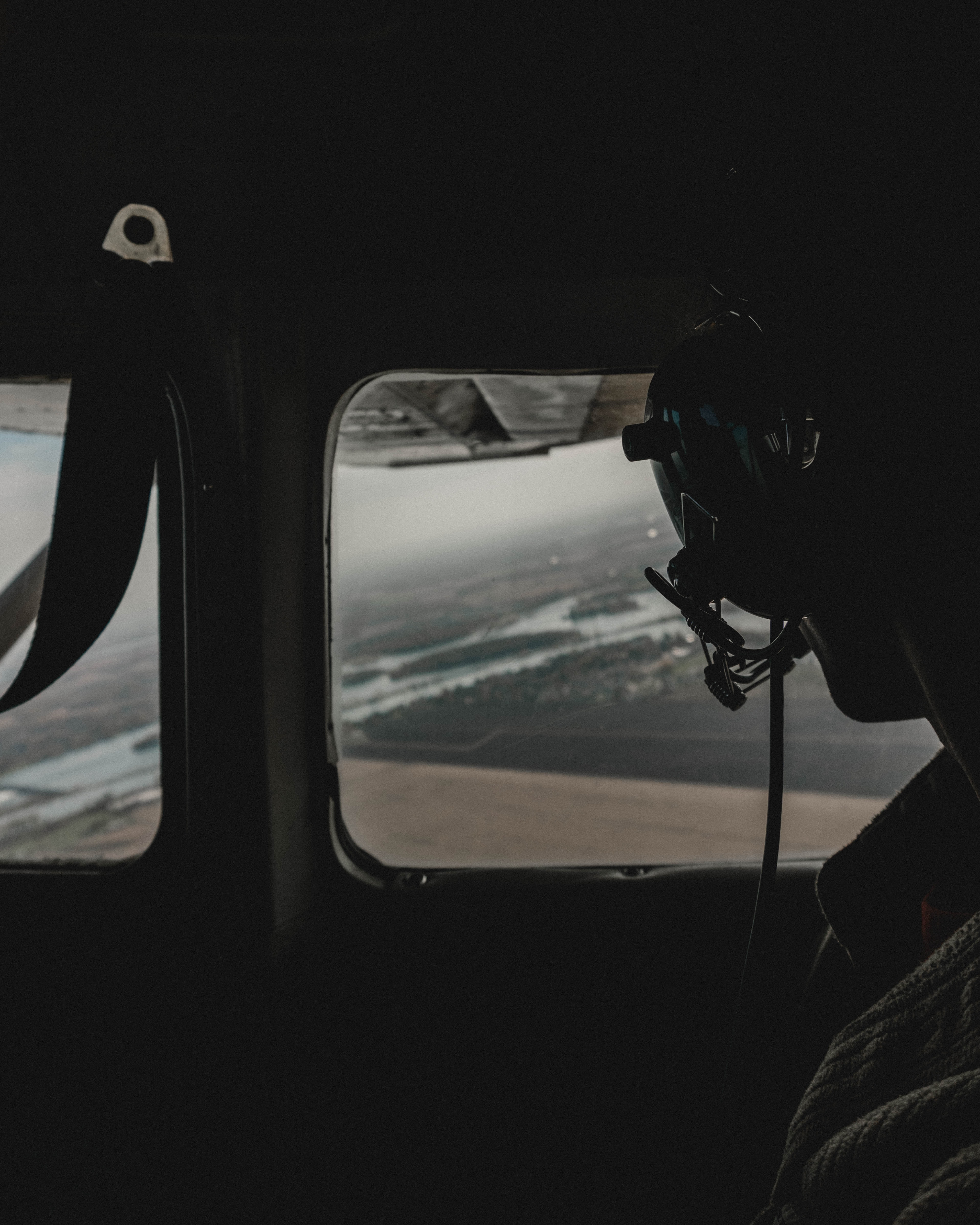 person wearing black headphones inside helicopter while looking down