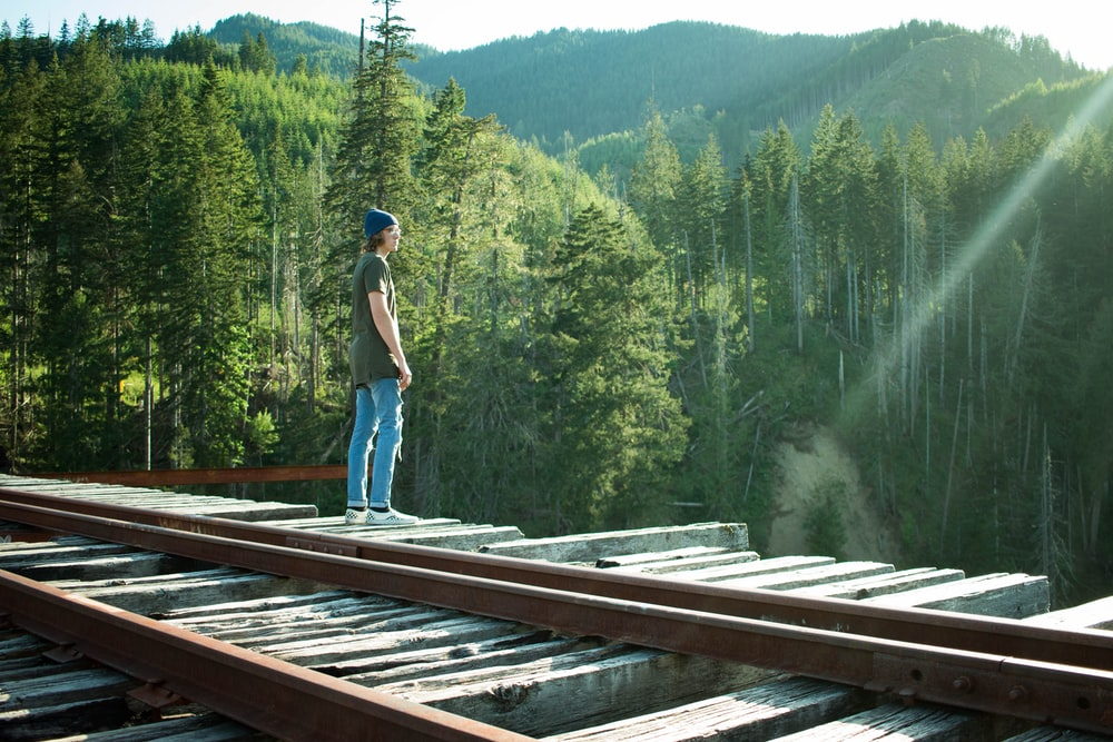 man standing on wooden bridge