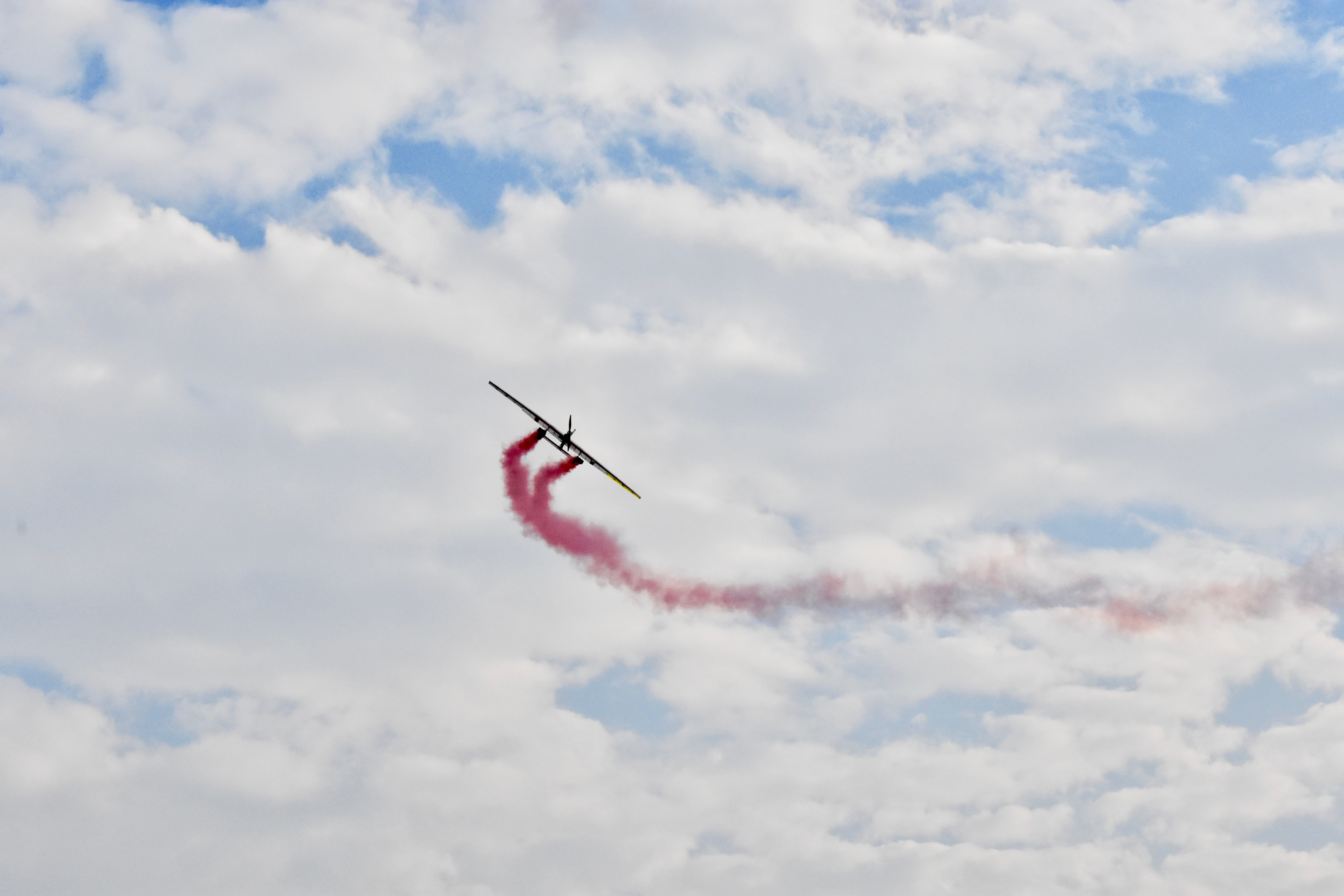 airplane releasing red smoke in mid air