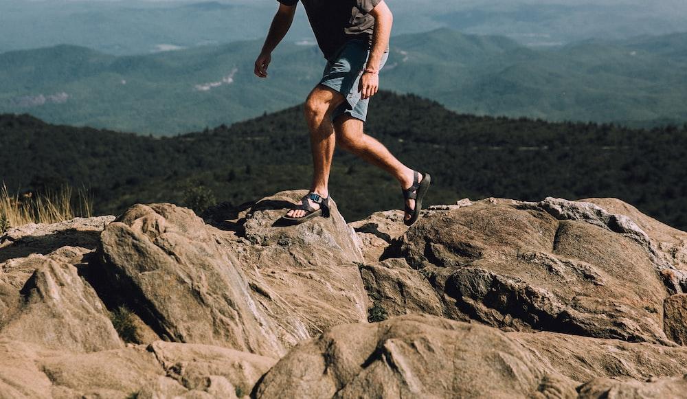 person in gray shirt walking on rocks