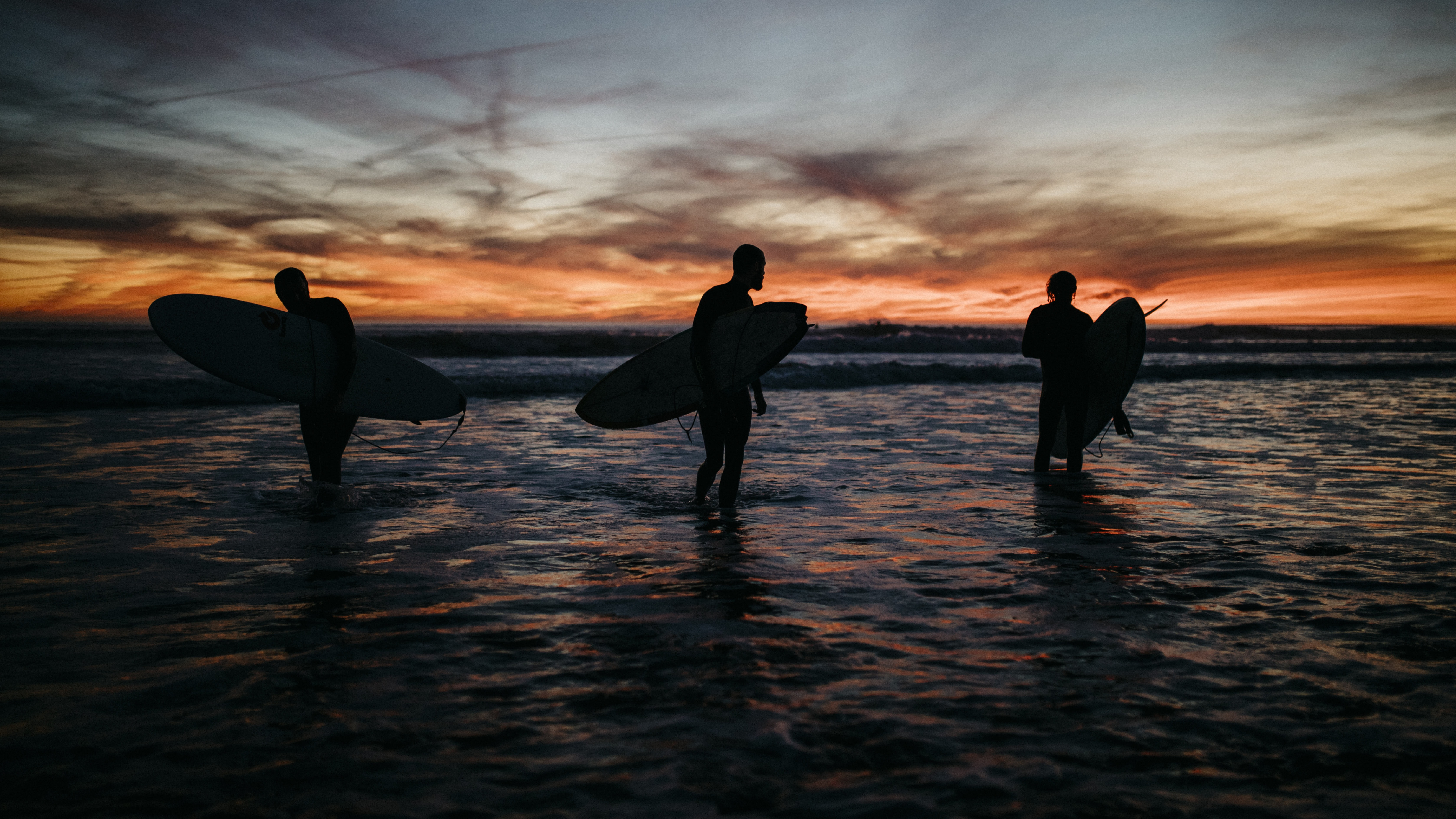 three people holding surf boards in ocean