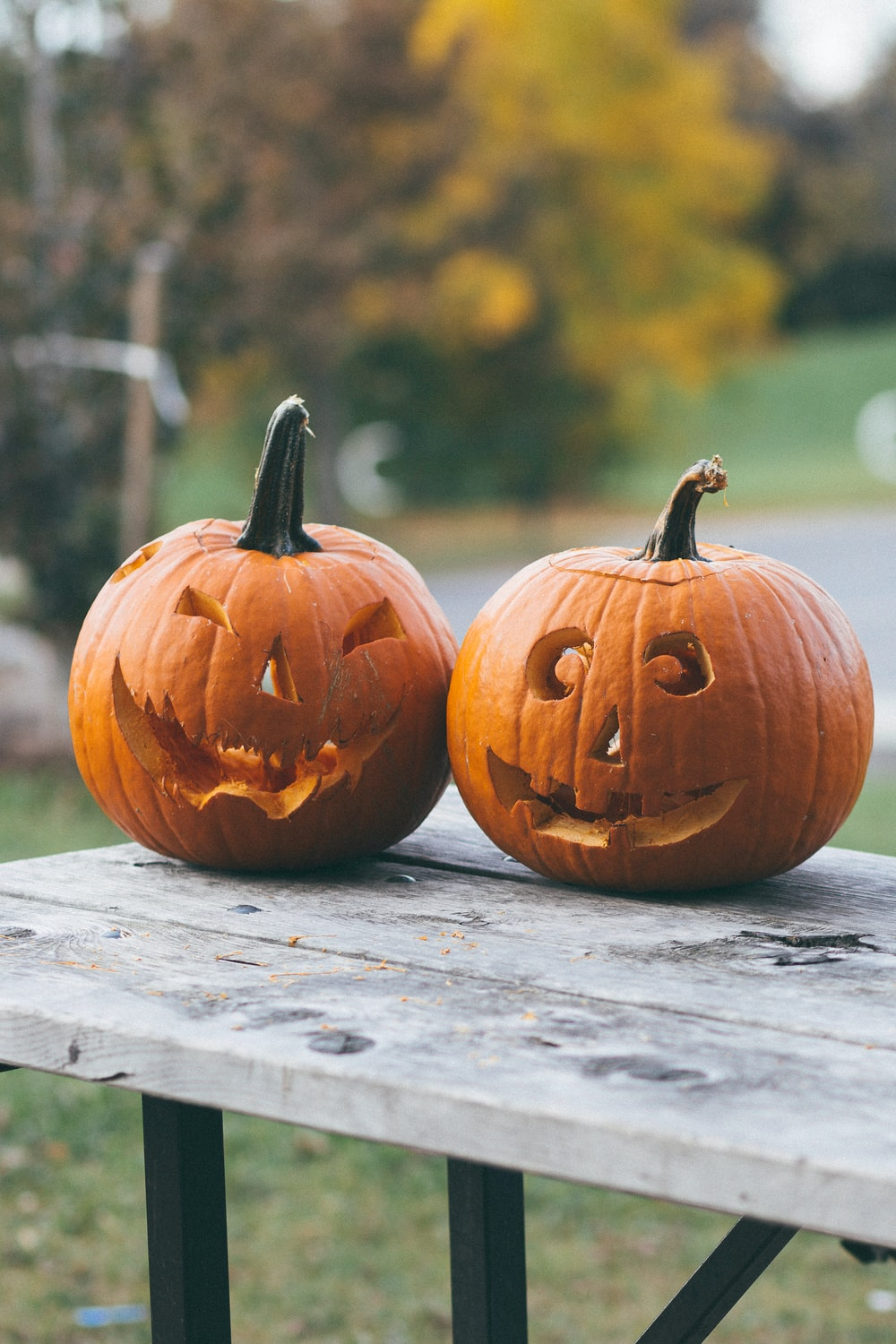 two pumpkins with faces carved on brown wooden table