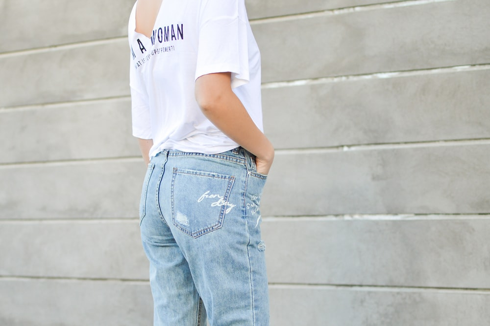 woman in white shirt and blue denim bottoms facing the wall