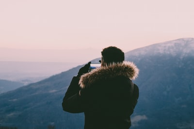 man taking photo on hills blurred zoom background