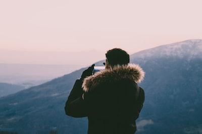 man taking photo on hills blurred teams background
