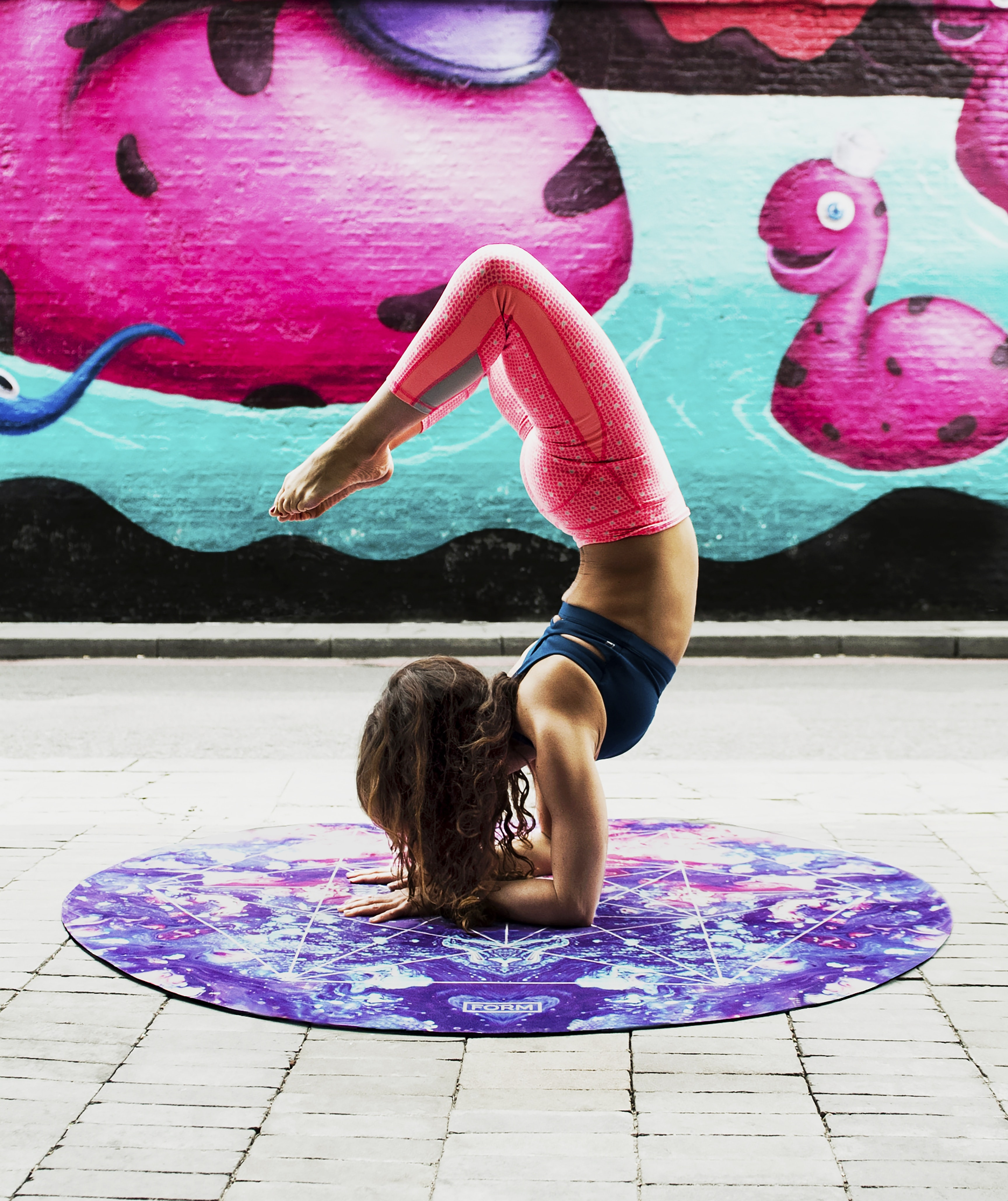 woman doing acrobats on purple mat during daytime