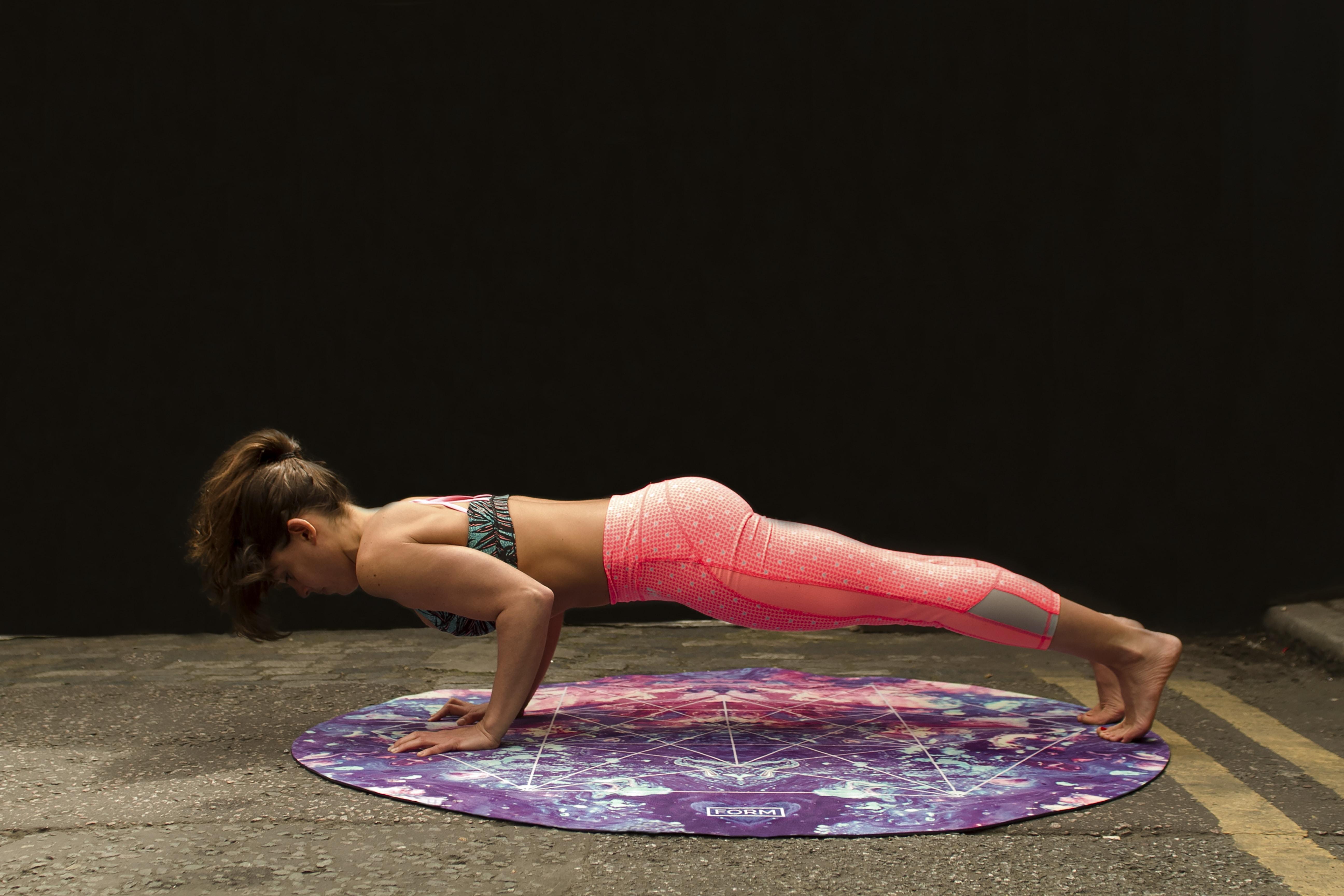 woman pushing up on yoga mat