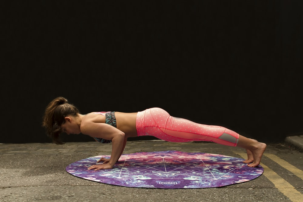 woman pushing up on yoga mat