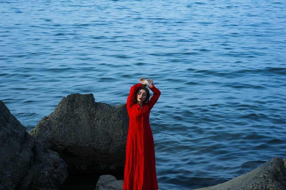 shallow focus photography of a woman standing on stone while raising her hands on her head