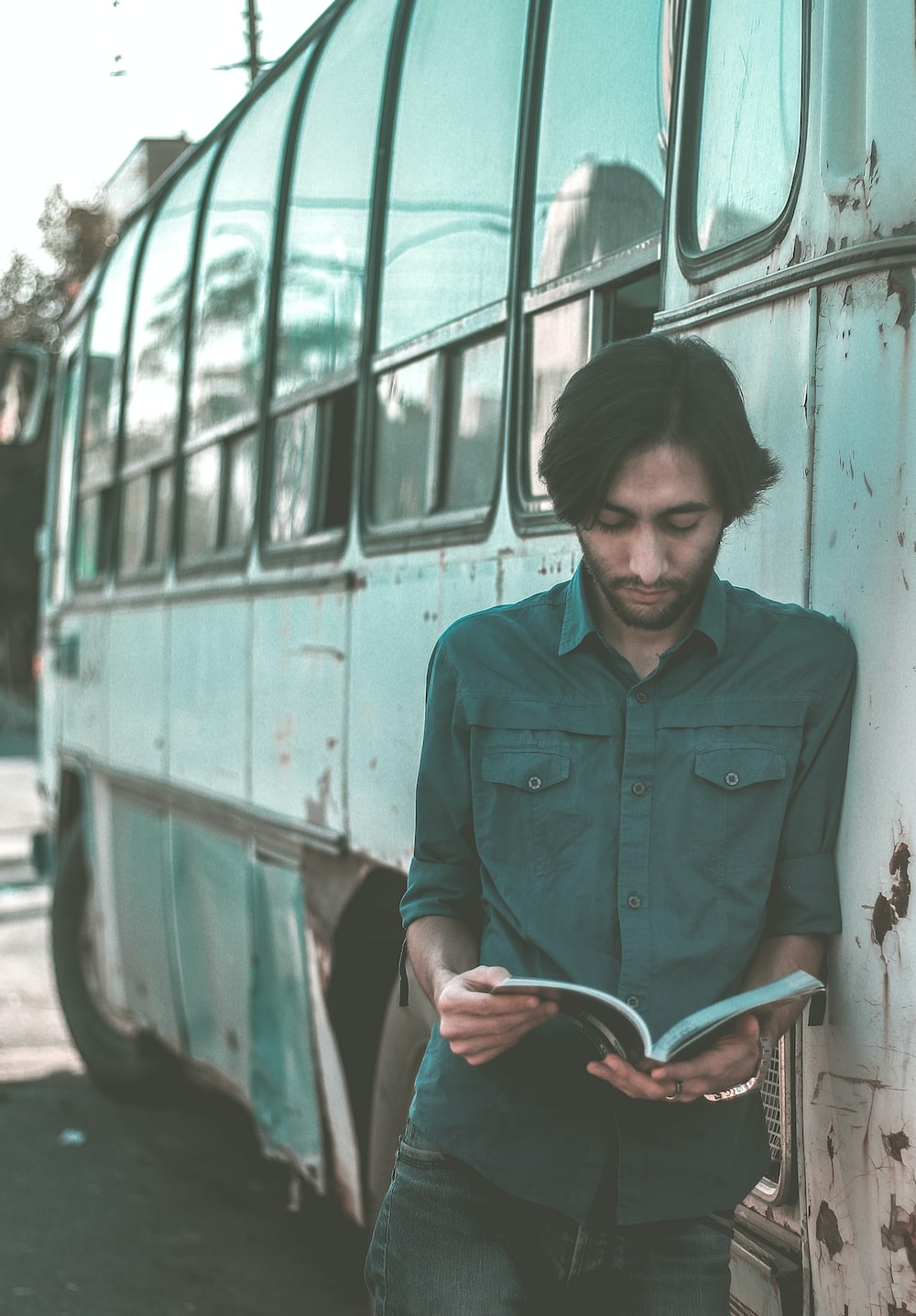 man reading book while leaning on bus