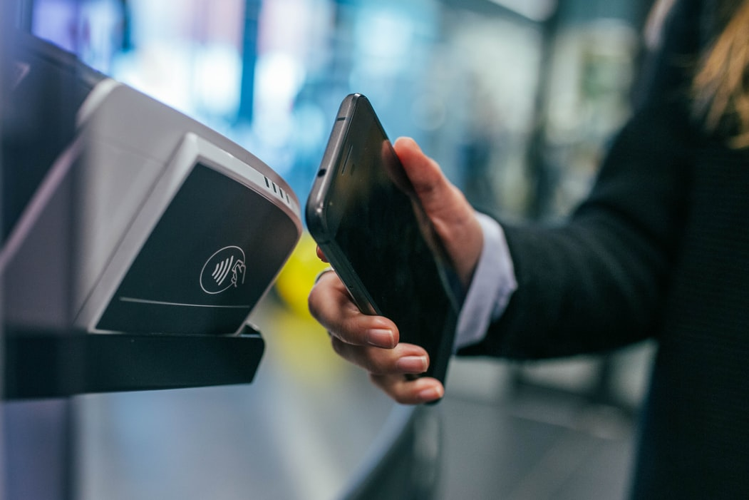 woman prepares to pay for her travel using contactless payment