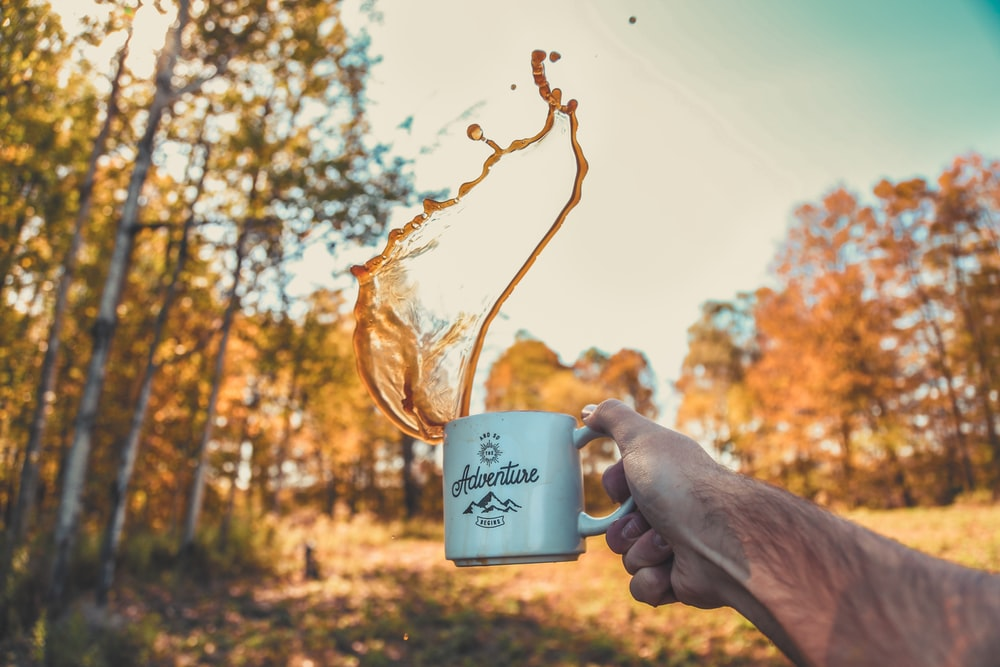 shallow focus photography of person spilling coffee from mug