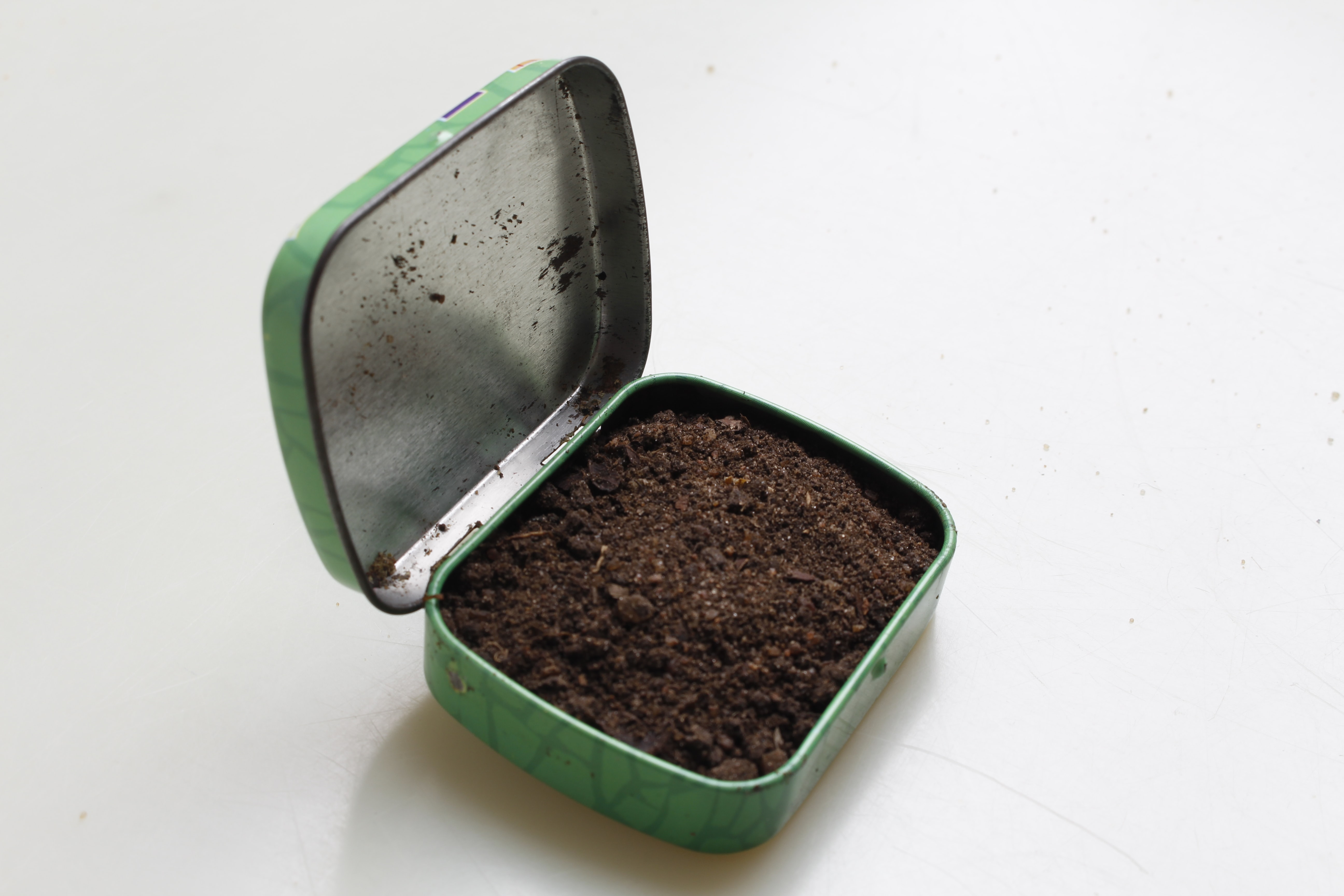 brown soil in green metal box