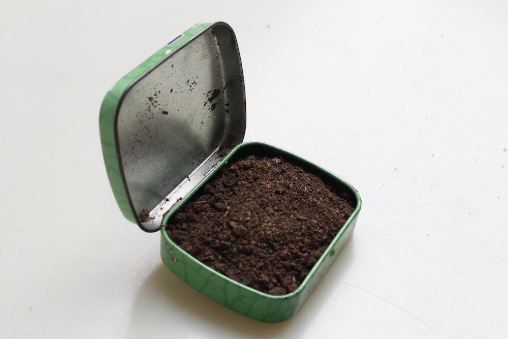 brown soil in green metal box