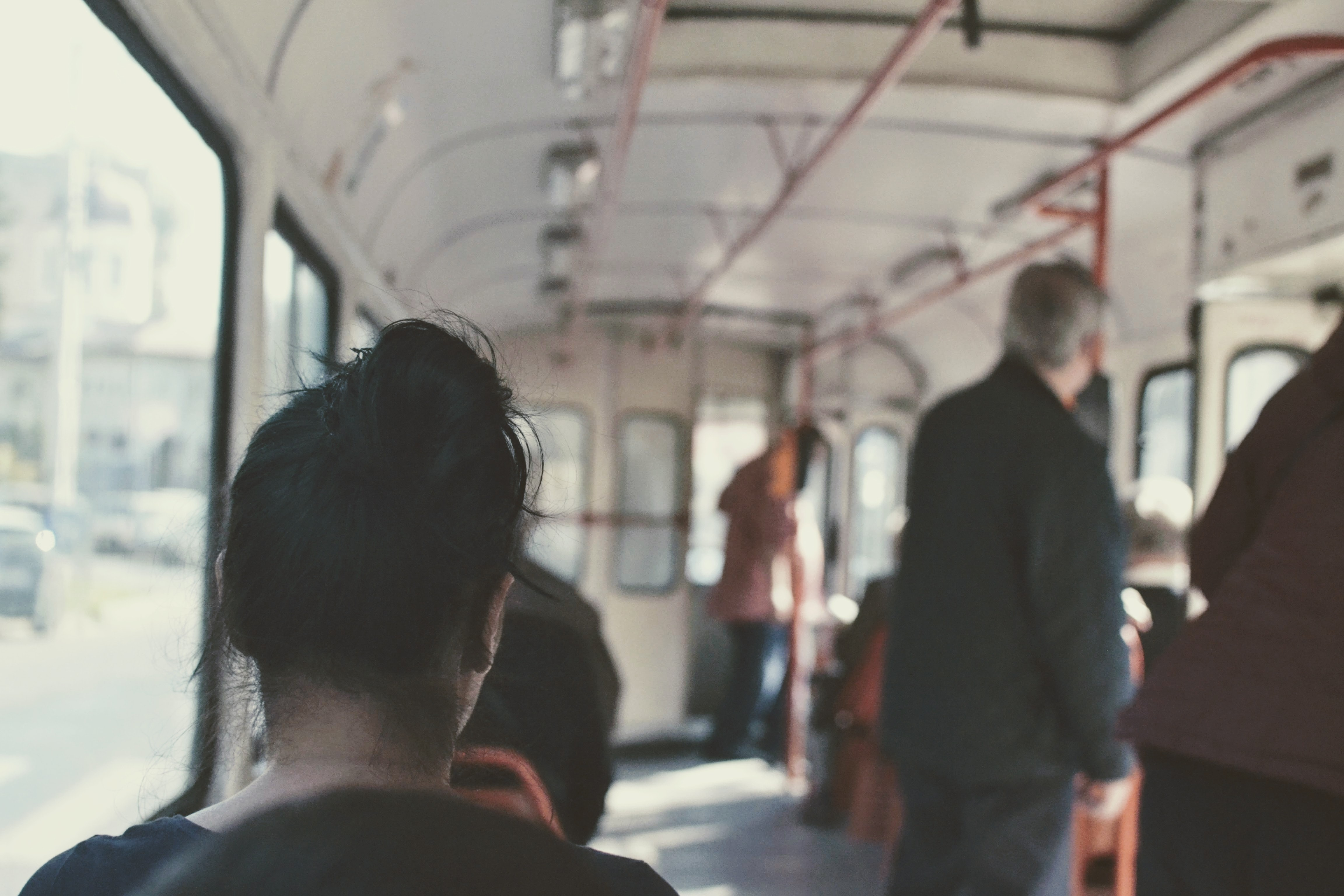 people sitting and standing in train