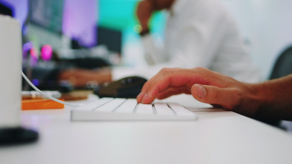 person holding white wireless computer keyboard on white wooden table inside room