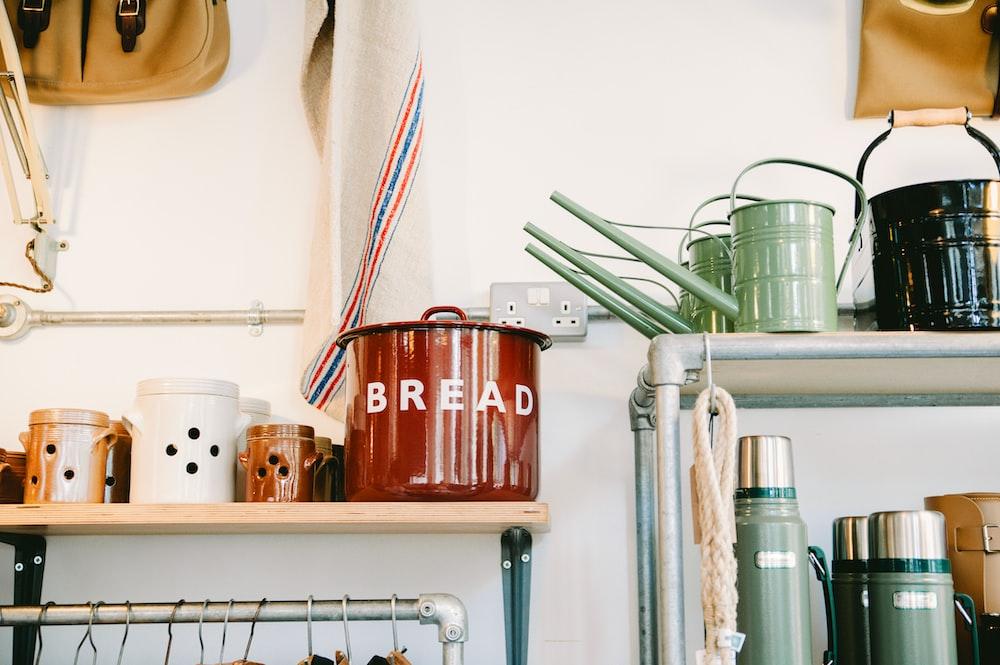 assorted-color ceramic canister on beige wooden rack inside room