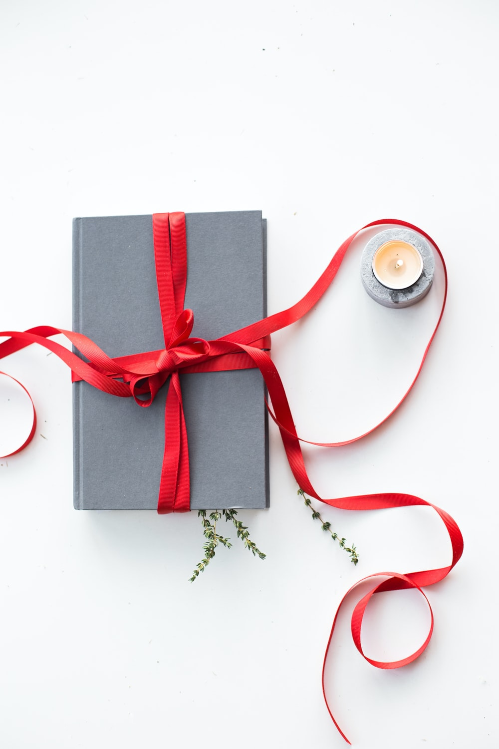 gray book wrapped with red ribbon beside teallight candle