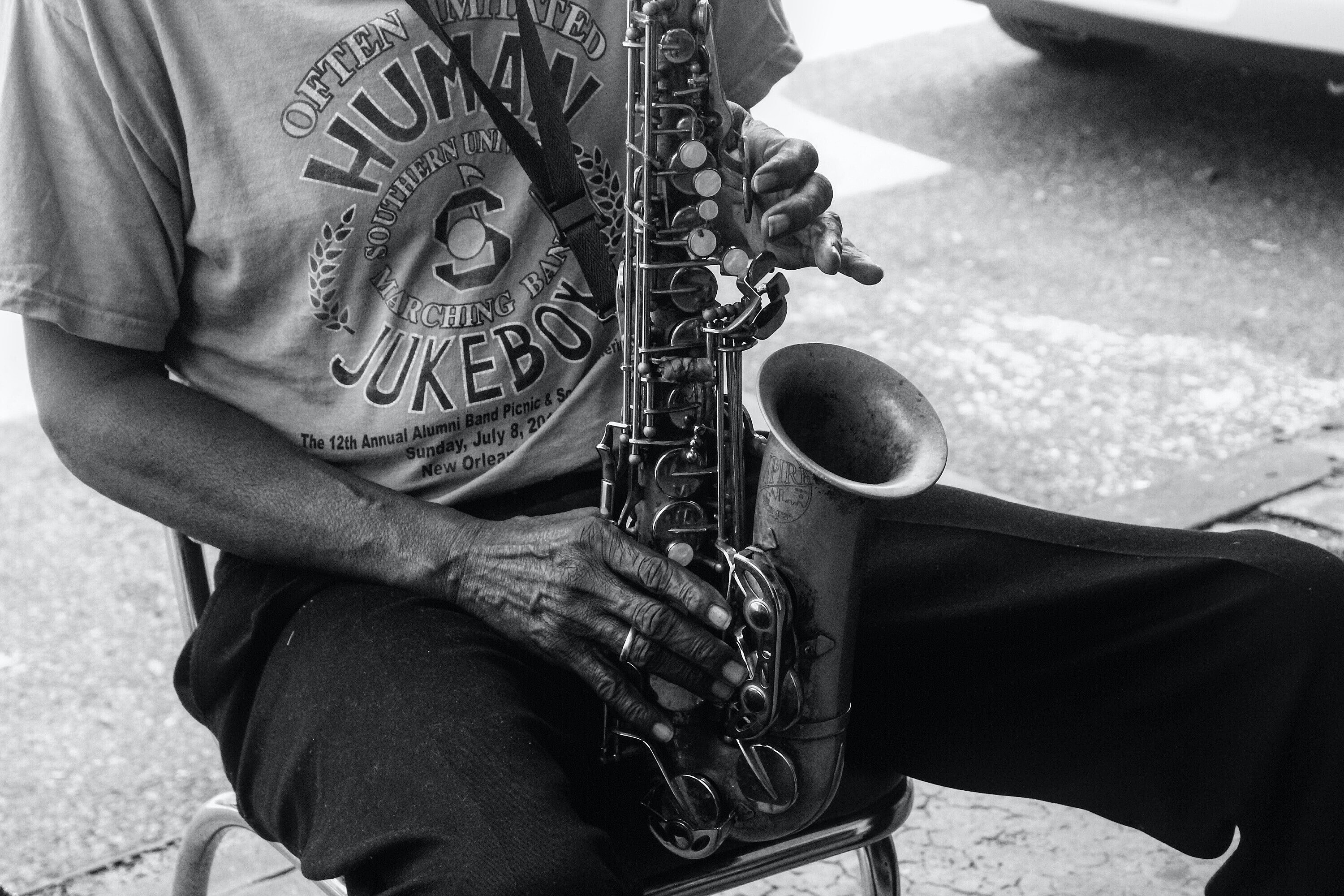 grayscale photo of a person playing saxophone while sitting