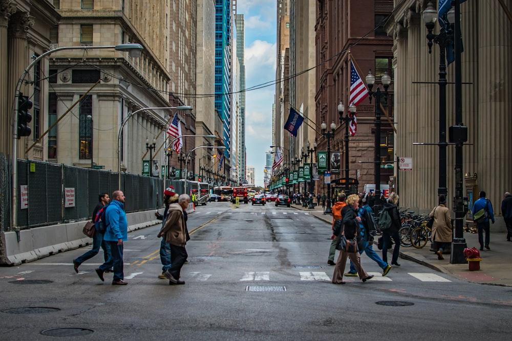 people crossing on pedestrian lane near buildings during daytime
