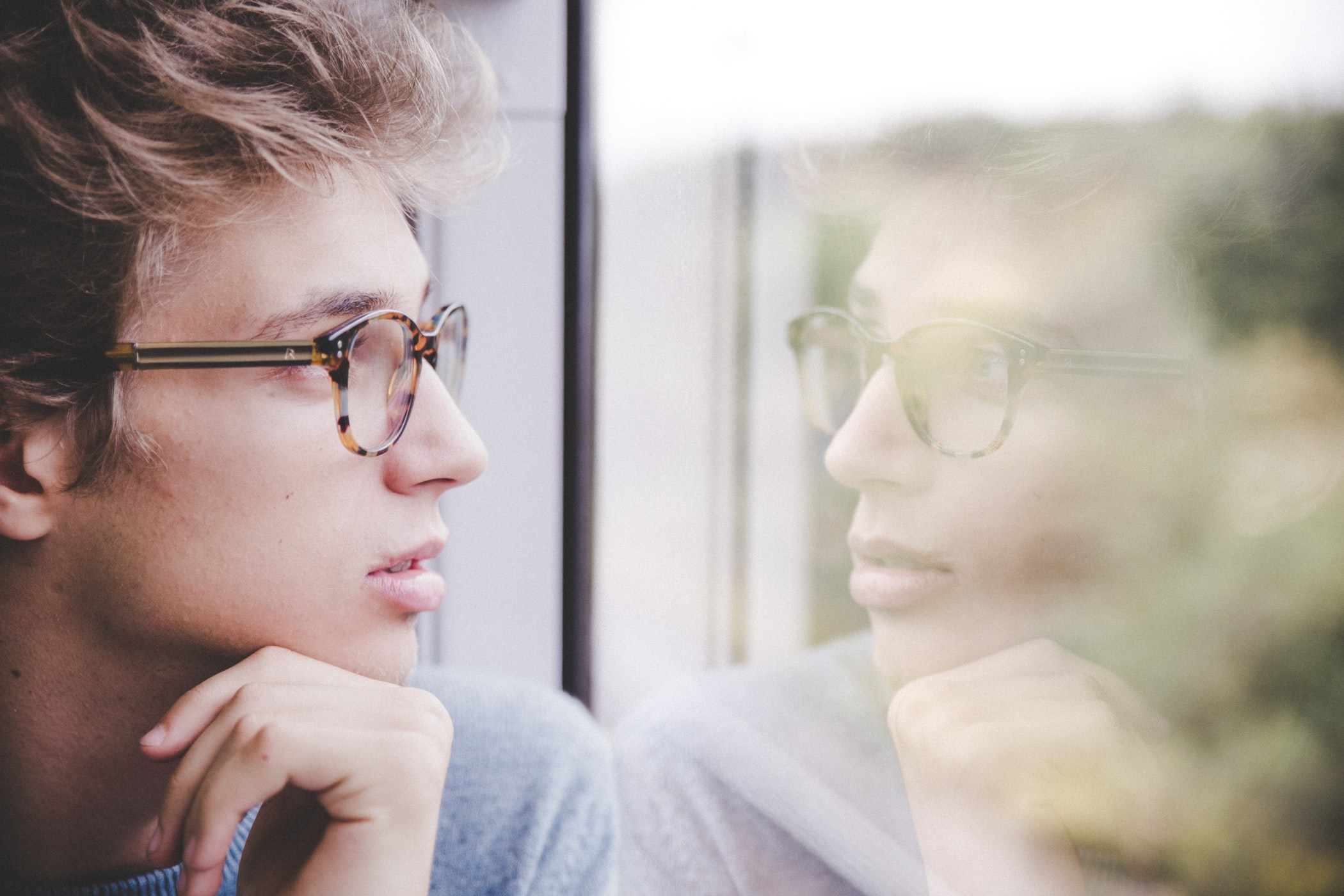 person reflecting and staring out the window