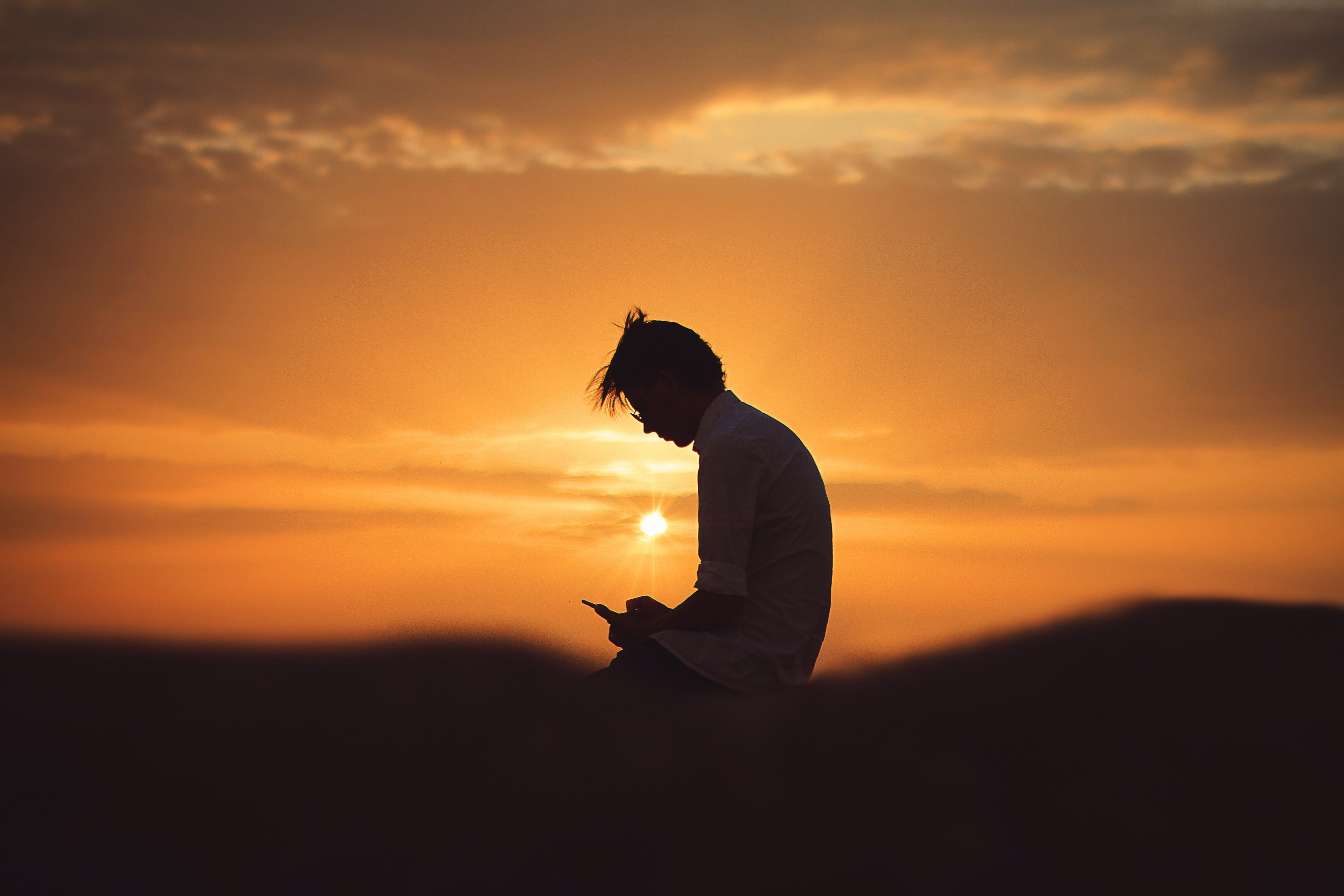 silhouette of man using smartphone during sunset