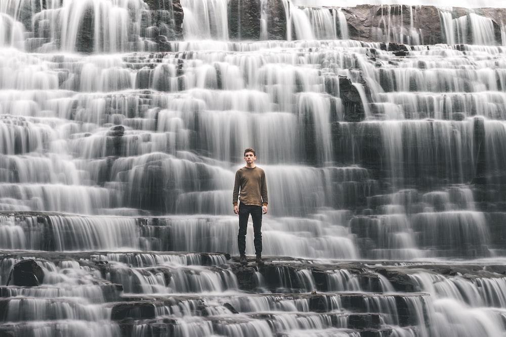 man standing on waterfalls