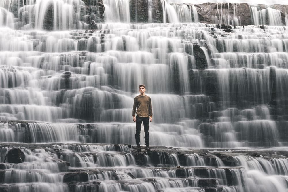 man standing on waterfalls