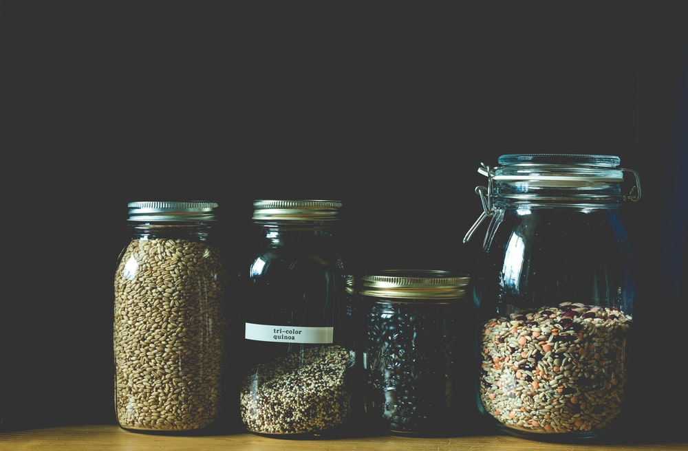 four clear jars filled with grains