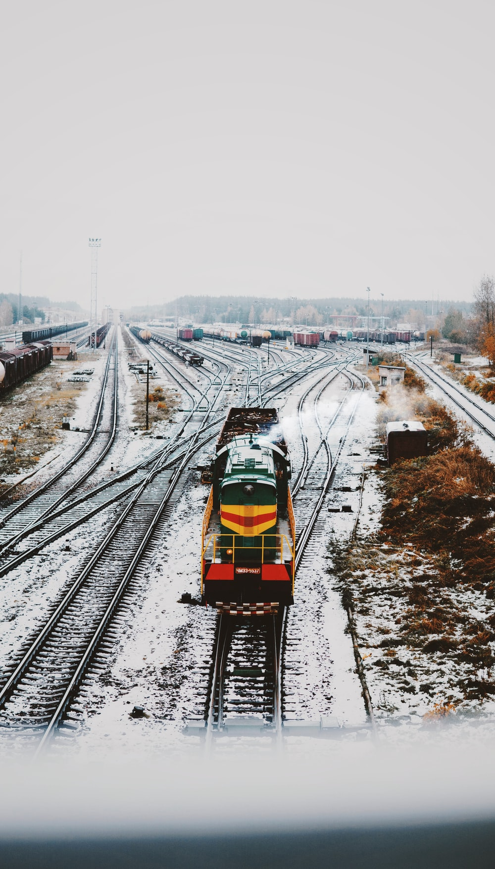 moving yellow and green locomotive train on train railways