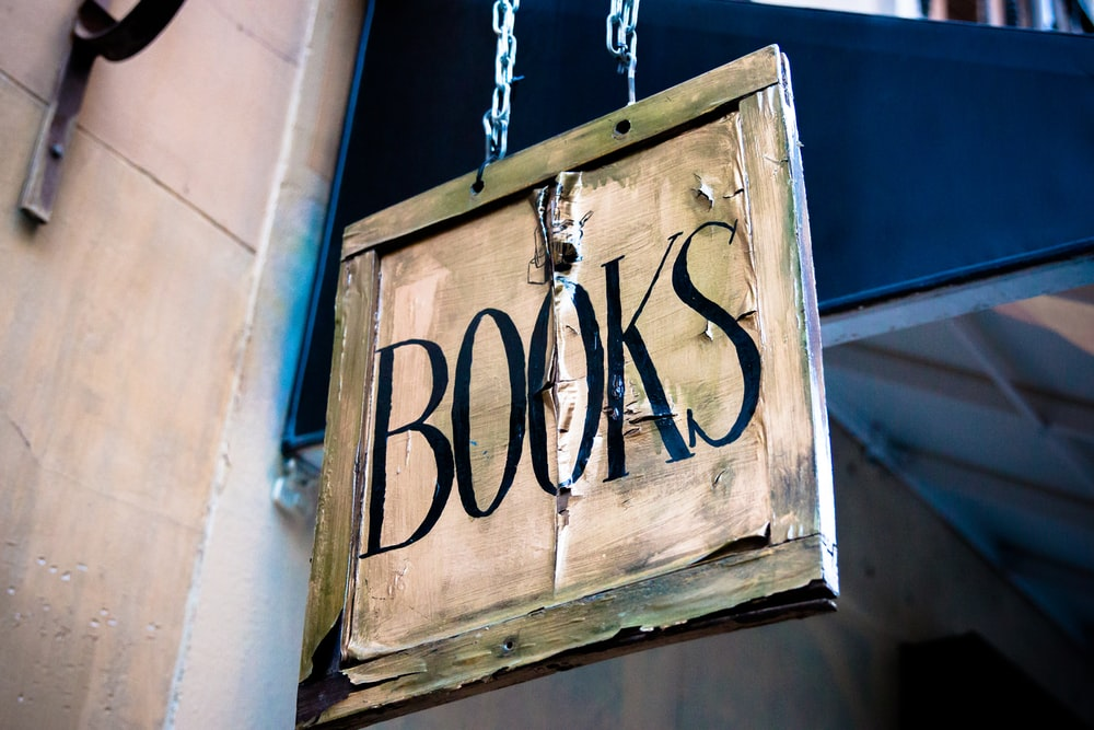book signage hanging beside white wall
