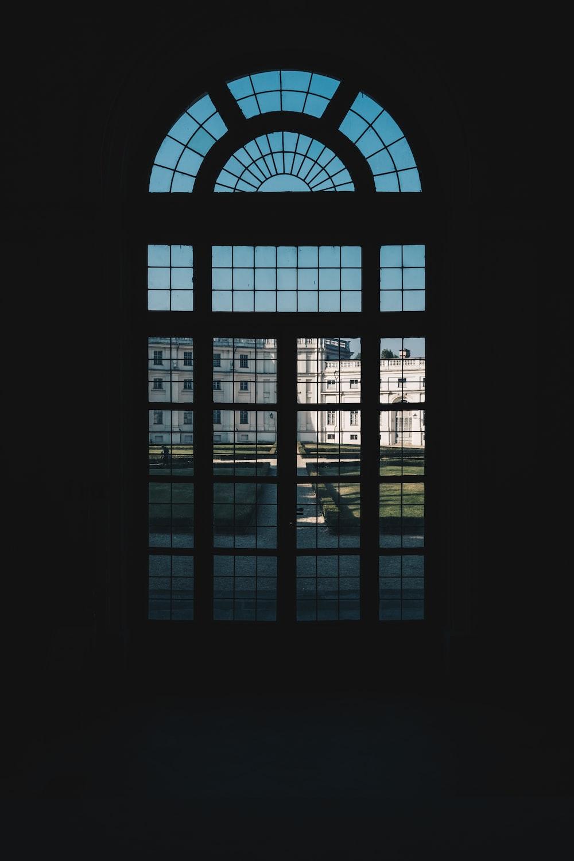 person in dark room near glass window