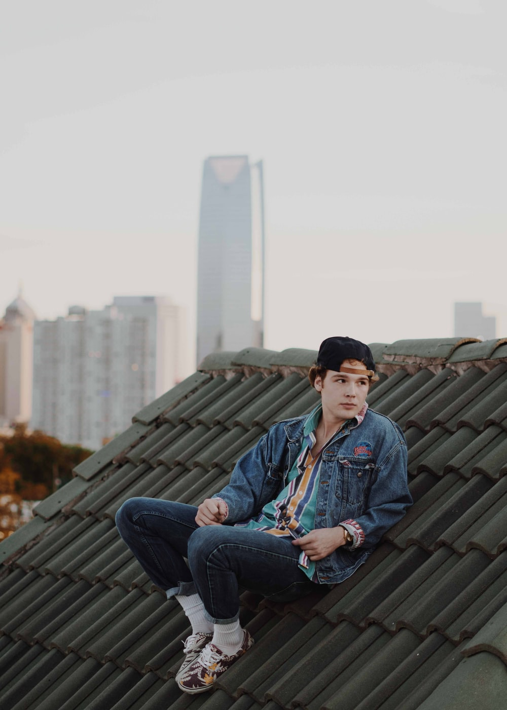 man wearing jacket and sitting on the roof