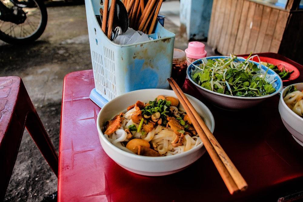 pair of brown chopsticks on white ceramic bowl