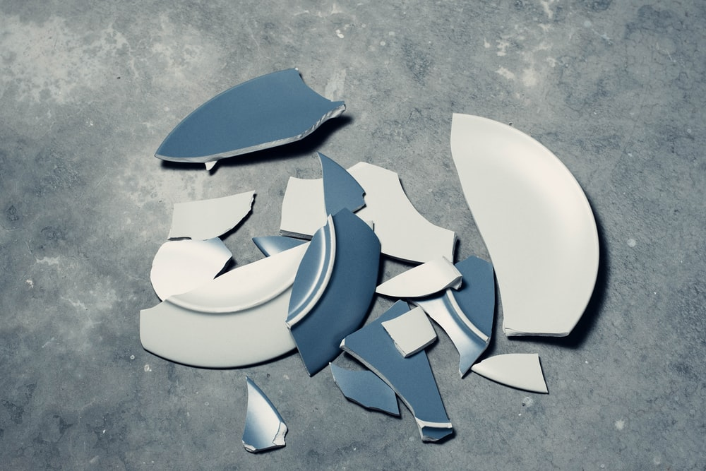 blue broken plate on gray concrete floor