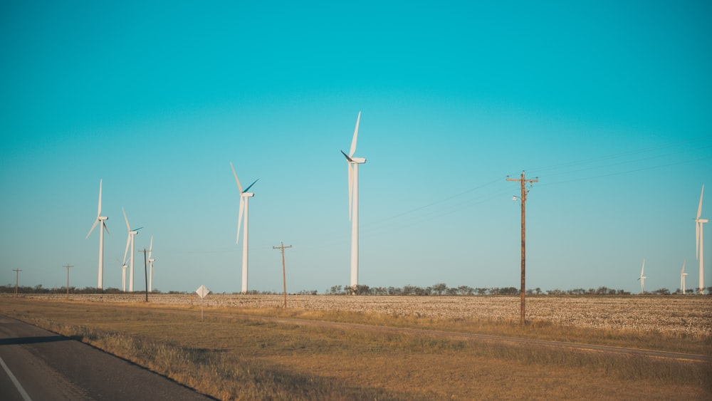 white windmills near asphalt road