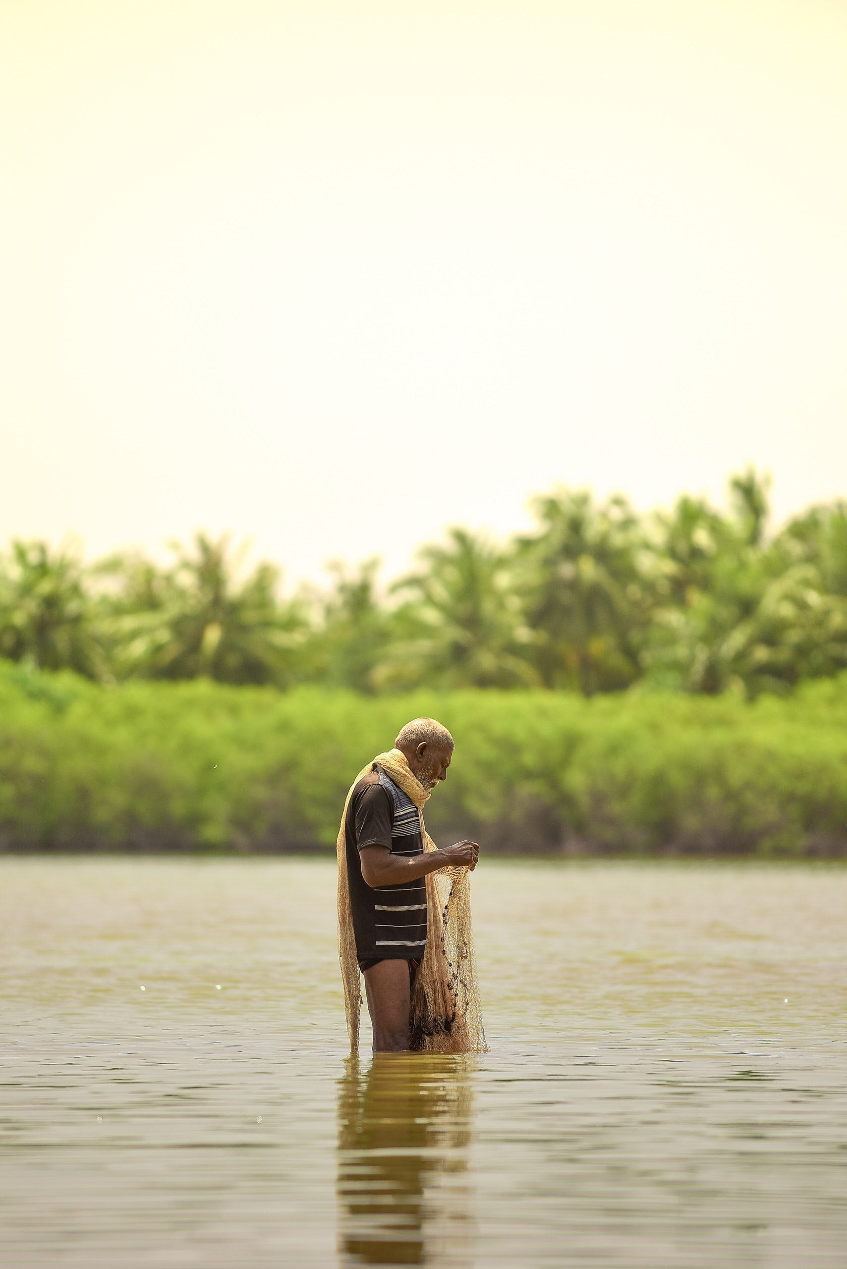 man holding fish net standing on body of water