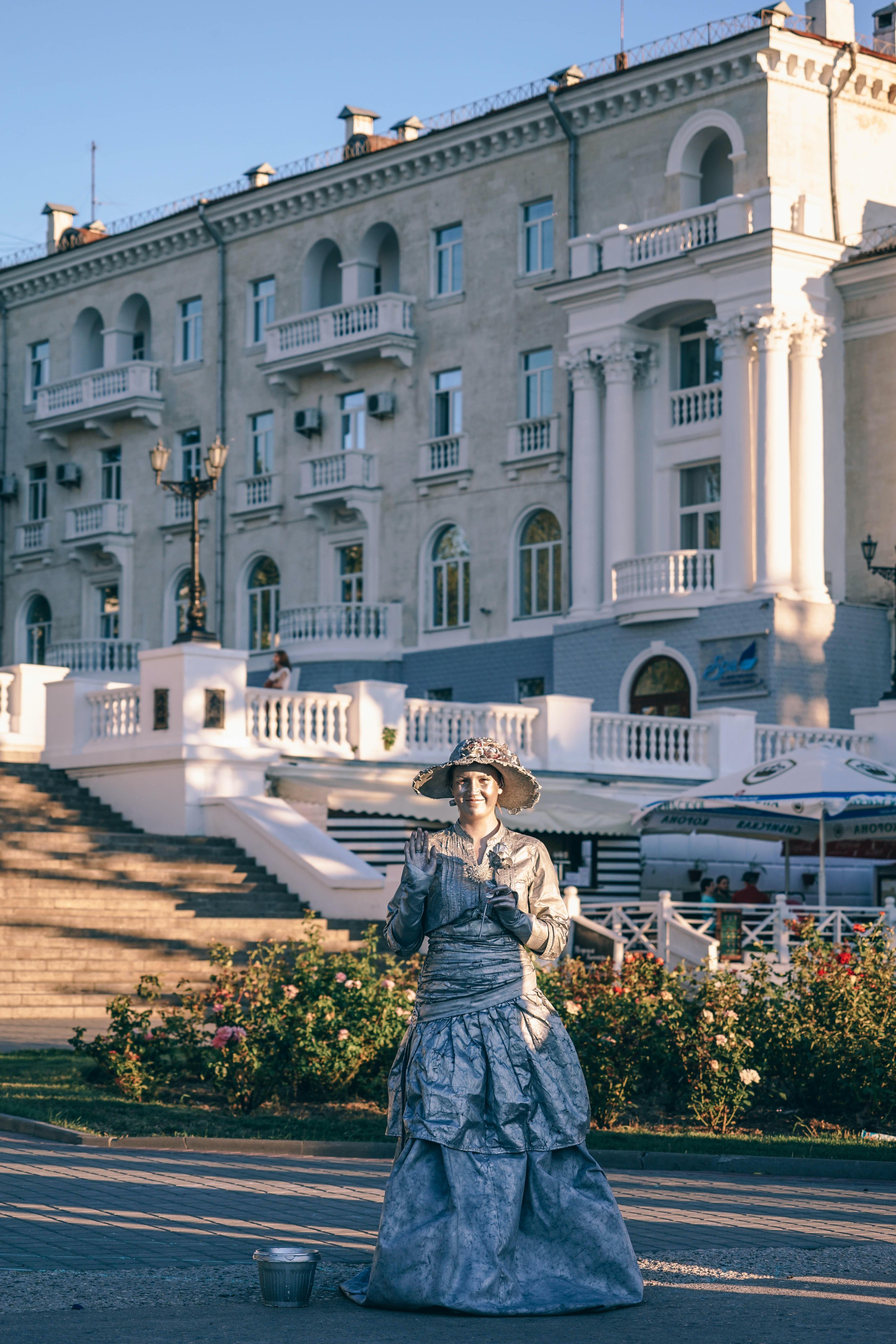woman standing in front white white concrete establishment