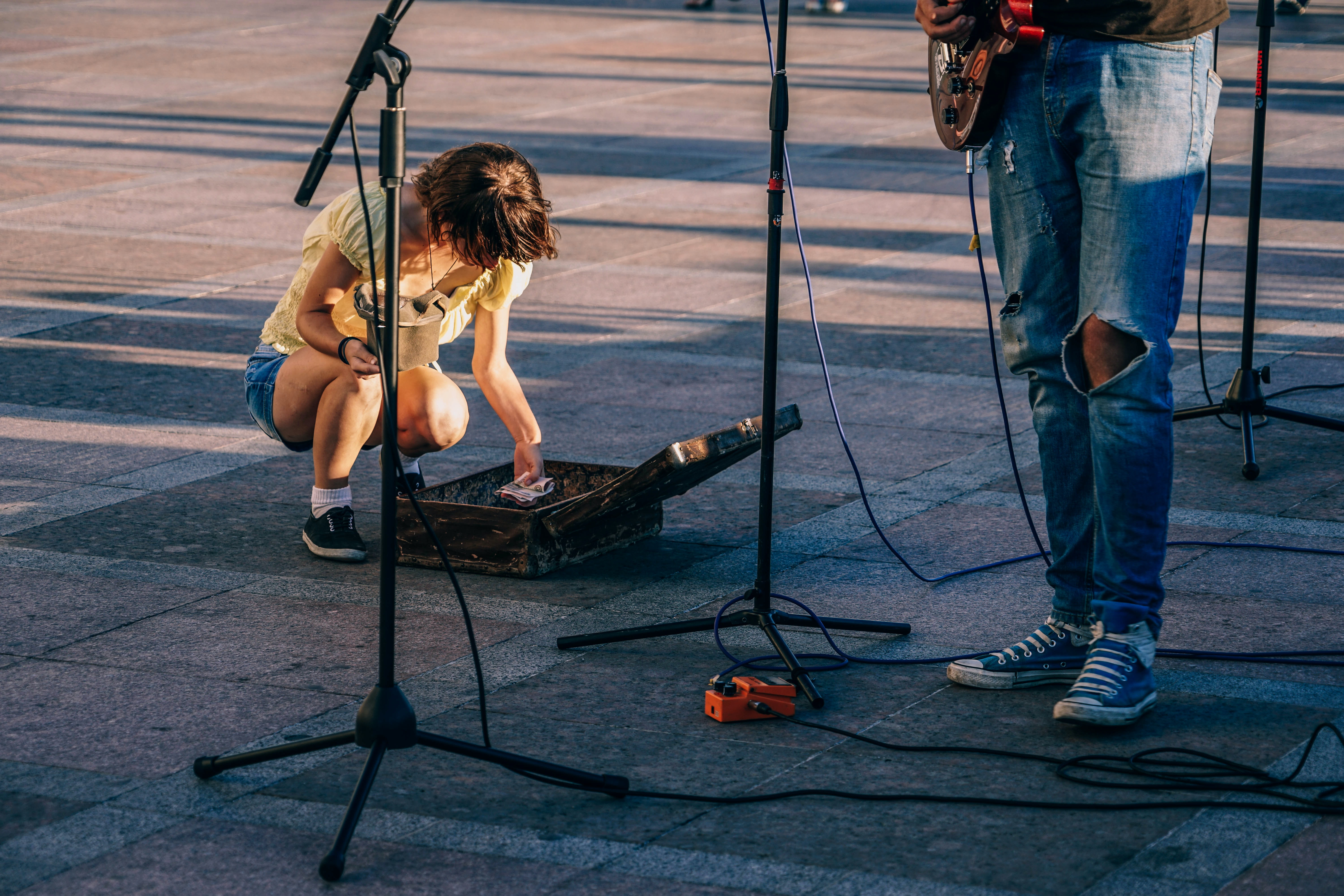 woman kneeling in front of person holding guitar