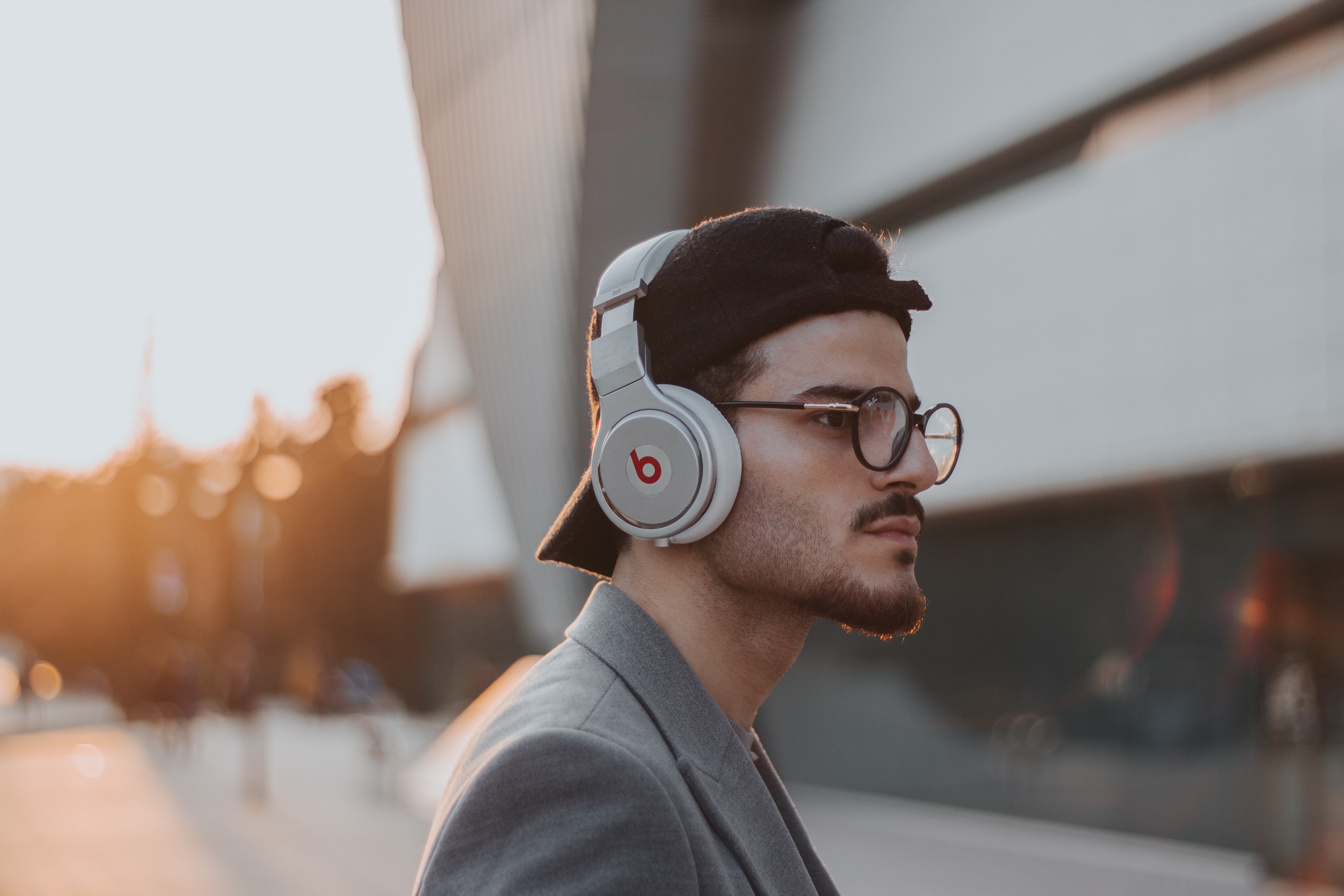 shallow focus photography of man wearing Beats wireless headphones