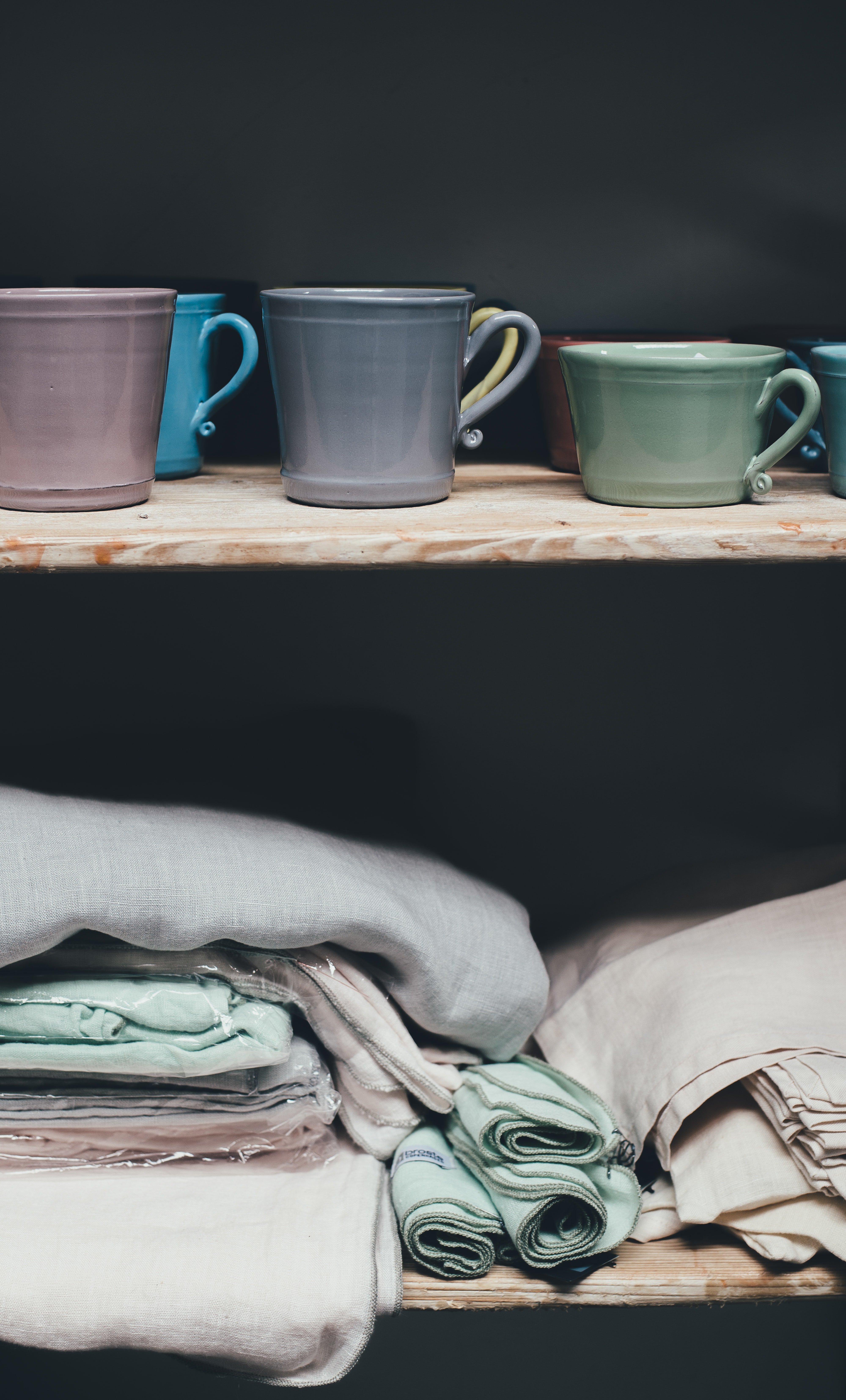 assorted-color ceramic mugs on top of shelf above piles of textile
