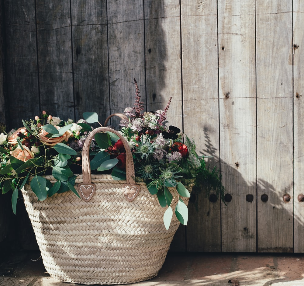 green and pink plant on woven basket