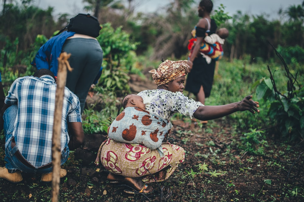 woman carrying toddler at back while planting