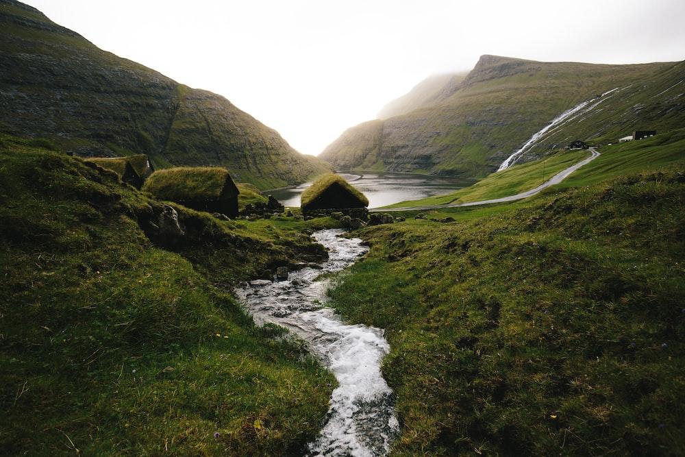water stream near green hills